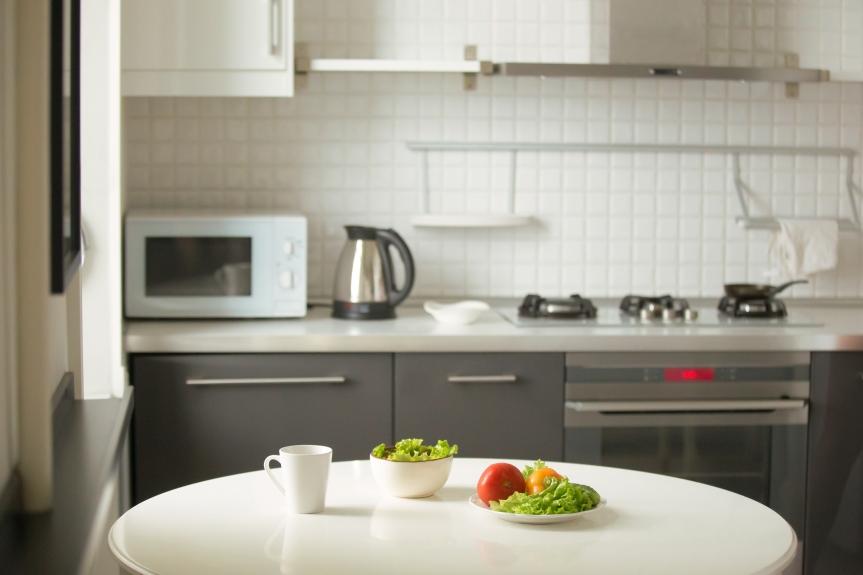 Modern kitchen, a white table, mug and green salad